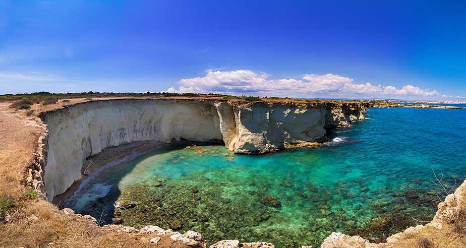 Splendida vista di un'insenatura rocciosa e di faraglioni all'interno dell'Area Marina Protetta del Plemmirio