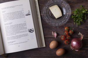 Tavola di legno con un libro di ricette siciliane sulla sinistra e sulla destra uova, aglio, cipolla, pomodorini, formaggio e prezzemolo
