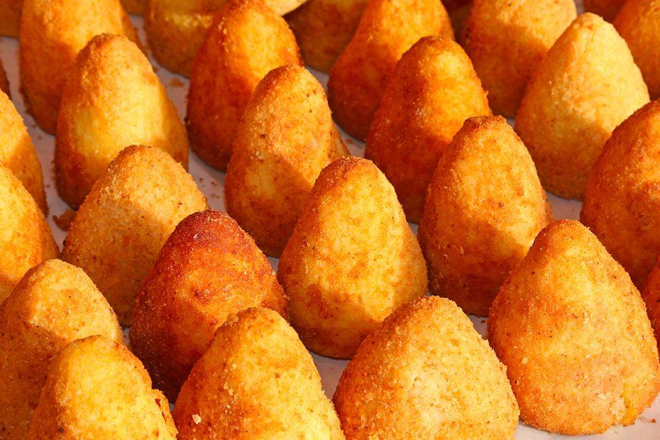Una serie di arancini siciliani esposti in una rosticceria
