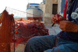 Un pescatore sistema le sue reti