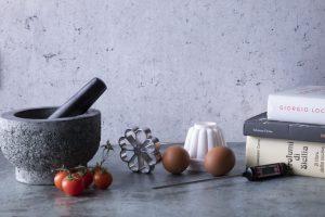 Libri di ricette siciliane e vari strumenti per cucinare come il mortaio e lo stampo per il bacio pantesco