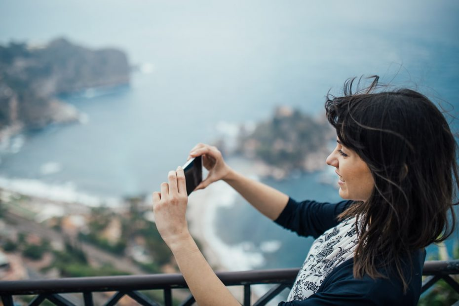 Una travel blogger scatta una foto a Taormina
